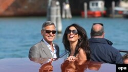 US actor George Clooney (L) and his fiance, Lebanese-British lawyer Amal Alamuddin (R) arrive in Venice, 26 September 2014