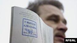 """Анатоль Лябедзька трымае пашпарт, на якім стаіць пячатка """"У выездзе адмоўлена"""""""