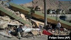 Люди біля зруйнованого землетрусом будинку в місті Дарбандіхан на півночі Іраку, 13 листопада 2017 року