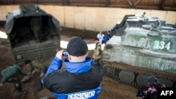 An OSCE monitor shoots video as Russia-backed separatists unload mortars from a truck near Donetsk.