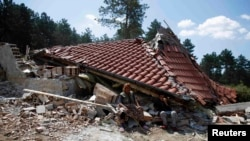 A Bulgarian Romany woman sits in front of her house after it was demolished in a Romany suburb of the city of Stara Zagora in July 2014.