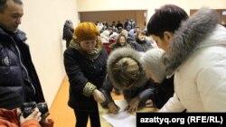 Жители села Березовка в Западно-Казахстанской области ставят подписи под обращением к президенту страны с просьбой их переселить в связи с отравлением. 29 ноября 2014 года.