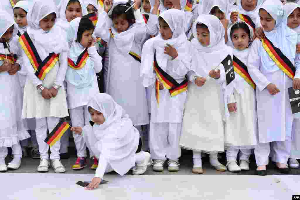 Girls hold flags during the inauguration of the Bait-ul-Wahid mosque in Hanau, Germany. (AFP/dpa/Boris Roessler)