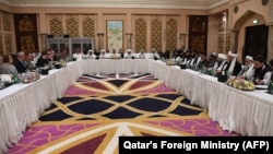 Qatari officials (center) take part in a meeting between U.S. special envoy Zalmay Khalilzad (second from left) and the U.S. delegation, and Sher Mohammad Abbas Stanikzai (sixth from the right) and the Taliban delegation, in Doha on February 26.