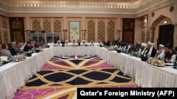 FILE: Qatari officials (C) take part in meeting between U.S. special envoy Zalmay Khalilzad (2nd-L), and the U.S. delegation, and Sher Mohammad Abbas Stanikzai (6th-R), and the Taliban delegation in Doha on February 26.