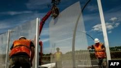 У французского города Кале рабочие возводят заграждение, которое должно защитить Евротоннель от нелегальных мигрантов.