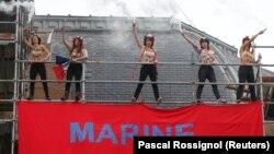 Активистки движения FEMEN развернули плакат возле избирательного участка, где голосовала Марин Ле Пен. Энен-Бомон, 7 мая 2017 года.