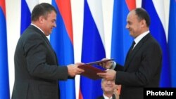 Armenia -- Defense Minister Seyran Ohanian (R) and his Russian counterpart Anatoly Serdyukov exchange copies of a newly signed Russian-Armenian military agreement, 20Aug2010.