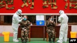 Сотрудники здравоохранения забирают пробы у сотрудниц военизированного подразделения полиции. Провинция Гуандун (Китай). 11 февраля 2020 года.