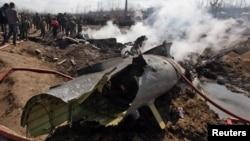 People stand next to the wreckage of an Indian Air Force's helicopter after it crashed in Budgam district. some 30 kilometers from Srinagar on February 27.