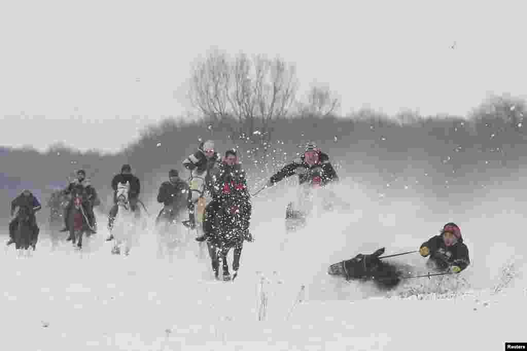 A horse and a rider fall in the snow during a race that followed a celebration of an Epiphany religious service in Pietrosani, Romania. (Inquam Photos/Octav Ganea via Reuters)