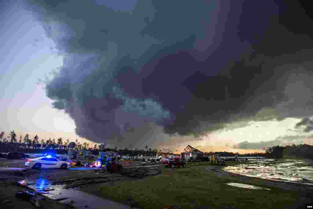 Storm clouds approach emergency crews at the scene of a house cut in half by a tornado near where seven people were killed outside Adel, Georgia, in the United States. At least 11 people were killed in Georgia during a severe weather outbreak. (epa/Mark Wallheiser)