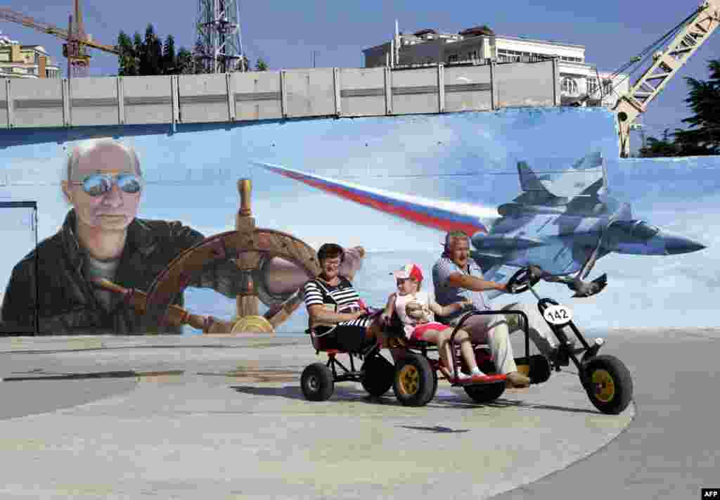 A family rides a quadracycle past a mural depicting Russian President Vladimir Putin in the Crimean city of Yalta. Crimea was illegally annexed from Ukraine by Russia last year. (AFP/Max Vetrov)