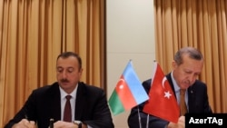 Azerbaijani President Ilham Aliyev (left) and Turkish Prime Minister Recep Tayyip Erdogan sign a protocol of the first meeting of Azerbaijan-Turkey High-Level Strategic Cooperation Council in Izmir on October 25.