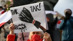 "A woman holds a placard reading ""Tick tock!"" as she attends an opposition rally in Minsk on October 26."