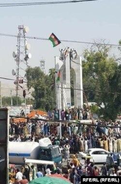معترضان در حال نصب بیرق سه رنگ افغانستان در شهر جلال آباد
