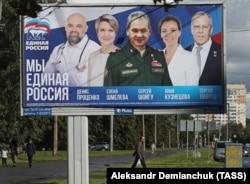 Мужчина проходит мимо рекламного щита партии «Единая Россия» в Санкт-Петербурге