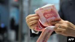 China -- A bank employee counts 100-yuan banknotes at a bank in Hangzhou, east China's Zhejiang province, December 1, 2015