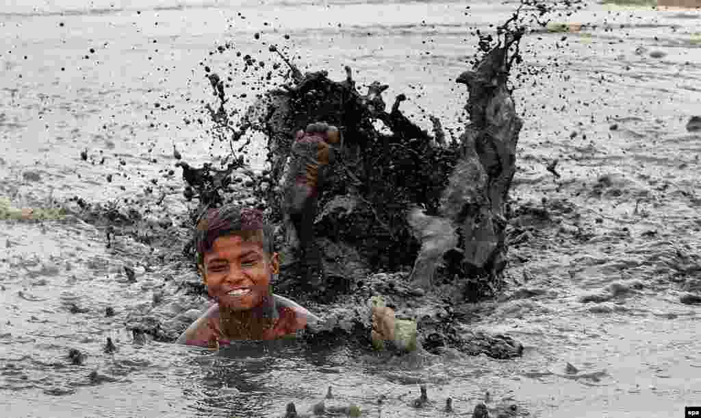 An Indian boy swims in a dirty pond in New Delhi on May 3. (epa)