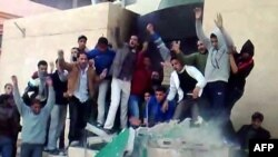A video grab shows anti-government demonstrators destroying a monument in Tobruk, Libya