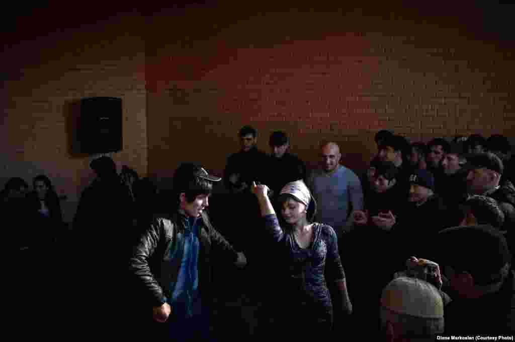 Party guests cheer as a couple dances Lezginka, a traditional dance in the North Caucasus.