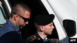 U.S. Army Private First Class Bradley Manning (right) is escorted by military police as arrives to hear the verdict in his military trial at Fort George G. Meade, Maryland on July 30.