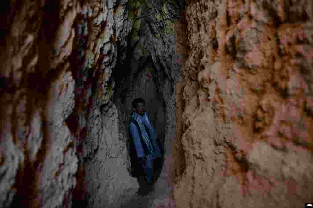Miner Morad Ali stands in a crevasse dug out of the side of a mountain.