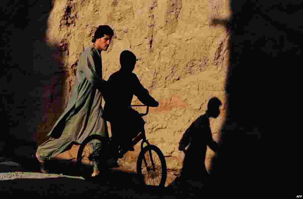 An Afghan child is silhouetted as he rides past a pedestrian in a street on the outskirts of Herat. (AFP/Aref Karimi)