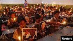 Nxënësit mbajnë qirinj dhe fotografitë e Nelson Mandelës gjatë një ceremonie të përkujtimit në një qytet të Indisë