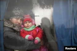 A woman and a child look through a bus window before being evacuated from Debaltseve.