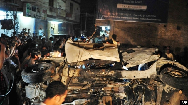 People gather around the destroyed car after the bomb explosion in Peshawar, which killed Nasrullah Afridi.