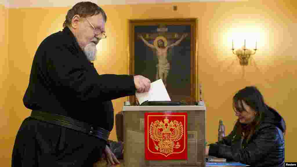 An Orthodox monk casts his ballot during the presidential elections at the Nilova Pustyn monastery near the town of Ostashkov