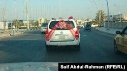 العروسان داخل سيارة ضمن موكب زفافهما في شوارع الكوت