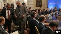 Участника делегации сирийской оппозиции выводят из зала во время межсирийских переговоров в Астане. 4 мая 2017 года.
