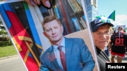 A protester holds up a picture of Sergei Furgal, the former governor, at a march in Khabarovsk on September 5.