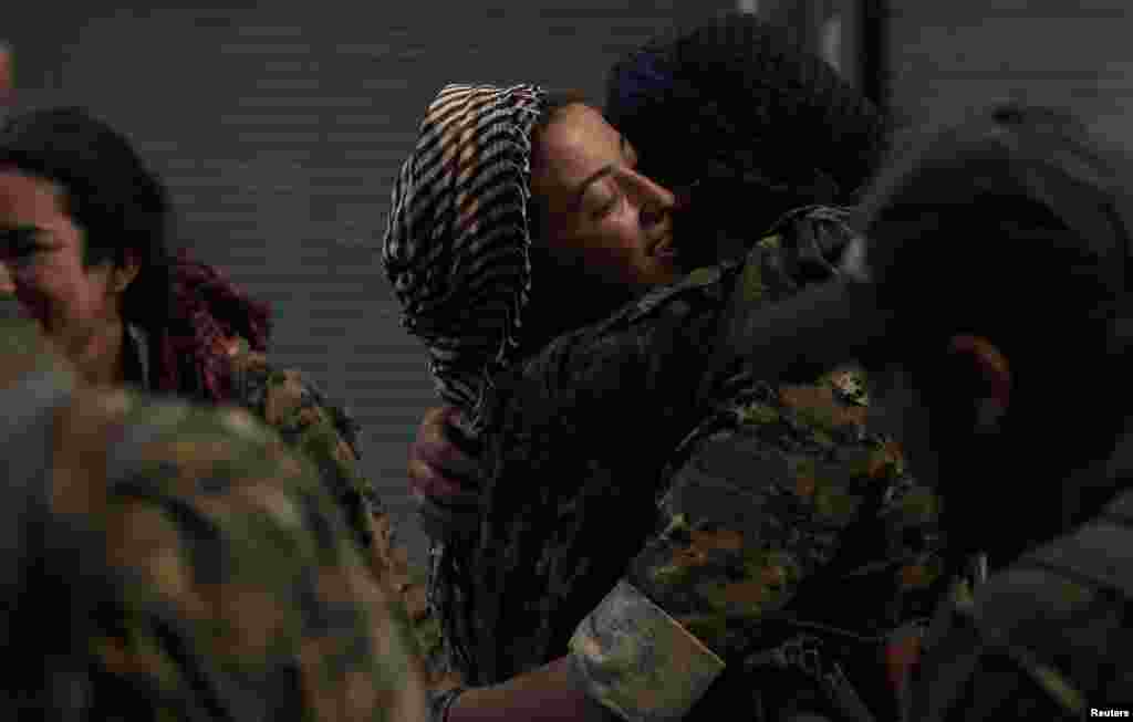 Female fighters with the Syrian Democratic Forces (SDF) embrace each other in the city of Manbij, in the Aleppo Governorate. (Reuters/Rodi Said)