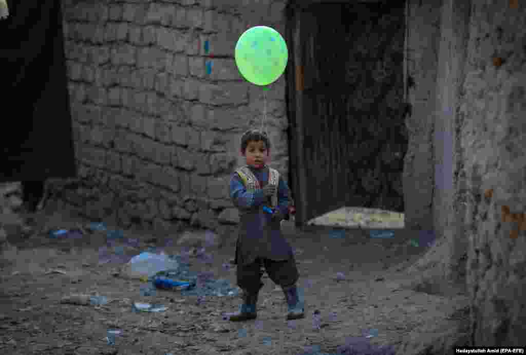 An Afghan boy poses for a photograph as he holds a balloon near a temporary shelter at an internally displaced persons camp on the outskirts of Kabul. (epa-EFE/Hedayatullah Amid)