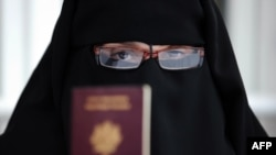 A Muslim woman wearing the niqab shows her passport in Montreuil, outside Paris.