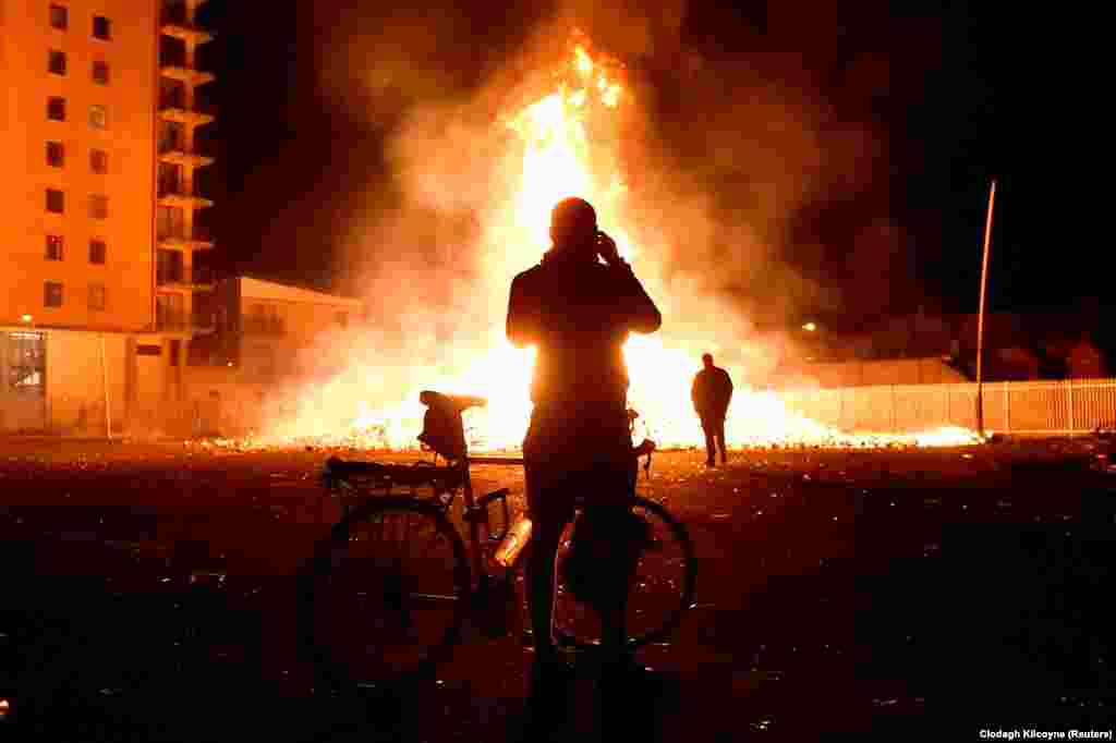 A man on a bicycle takes a picture of a bonfire in Belfast's Sandy Row area after it is lit by petrol bombs during  Twelfth of July celebrations held by members of pro-British Loyalist Orders in Northern Ireland. (Reuters/Clodagh Kilcoyne)