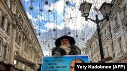 Активіст роздає летючки на підтримку кандидата у президенти Володимира Путіна в центрі Москви 16 березня 2018 року