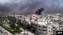 A video shows fire rising from reported shelling by Syrian government forces on the district of Khalidiya in the flashpoint central city of Homs on April 19.