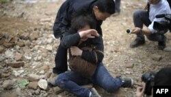 Женщина пытается защитить свой дом от сноса. Китай, провинция Гуандун, март 2012 года. Иллюстративное фото.