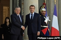 French President Emmanuel Macron (right) shakes hands with Uzbek President Shavkat Mirziyoev at the Elysee Palace in Paris on October 9.