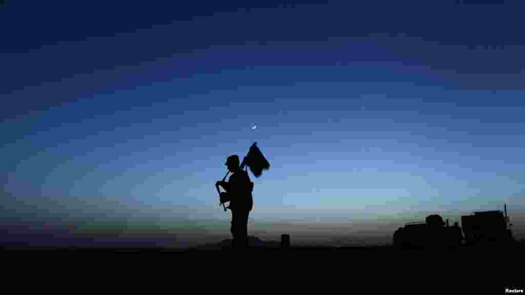 A U.S. Army piper plays the bagpipes at dusk in Zabul Province in Afghanistan on May 23. (Reuters/Tim Wimborne)