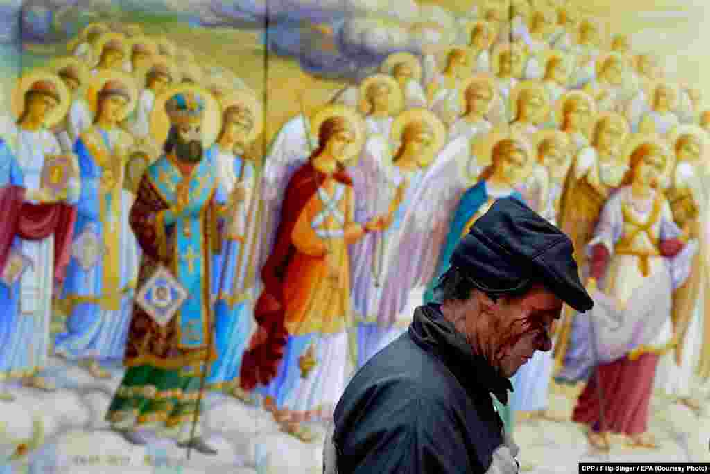 Czech Press Photo Photograph of the Year: A man wounded in clashes in Kyiv, Ukraine, walks past a religious painting. (epa/Filip Singer)