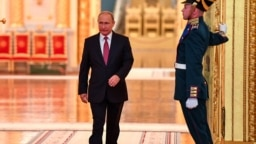 Russian President Vladimir Putin walks past an honor guard as he attends a ceremony at the Kremlin in Moscow.