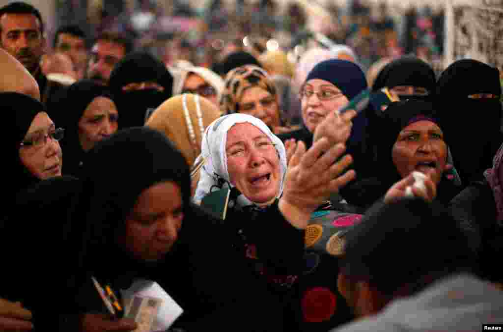 A woman cries as she asks for a travel permit to cross into Egypt through the Rafah border crossing after it was opened for two days by Egyptian authorities in the southern Gaza Strip on May 11. (Reuters/Suhaib Salem)