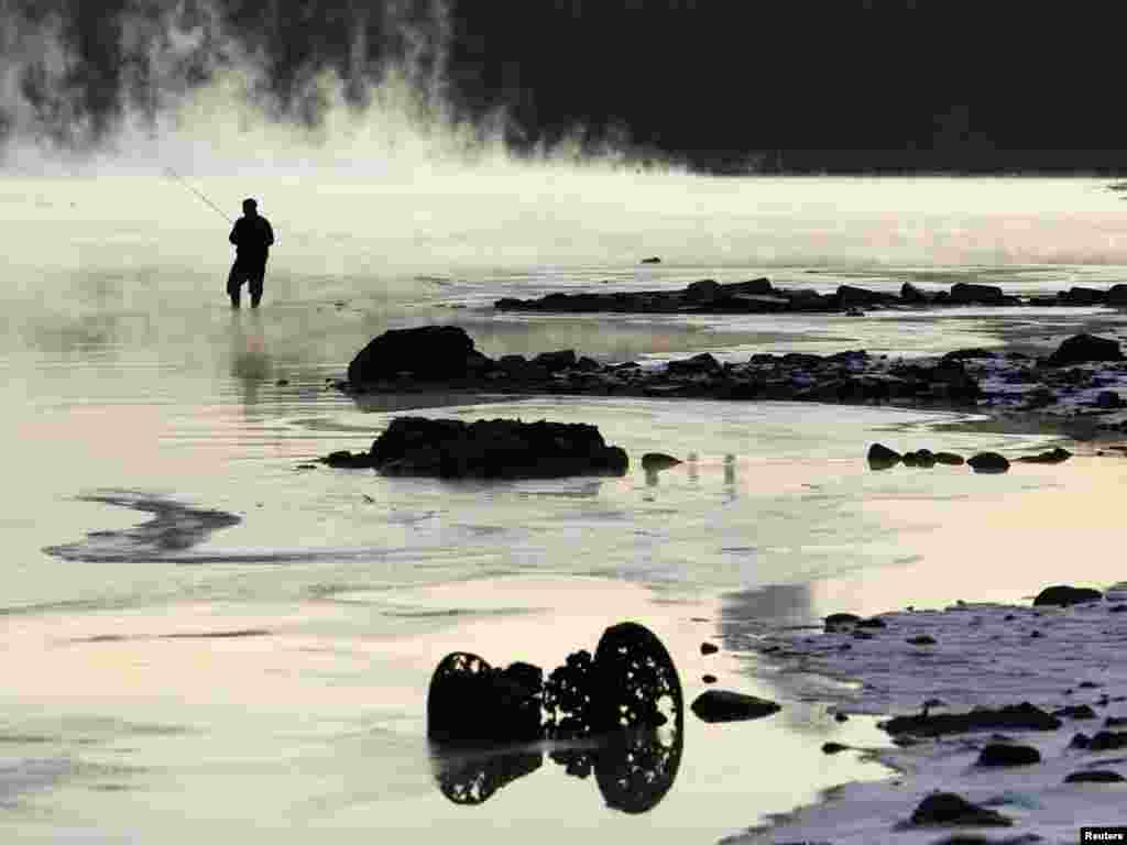 A fisherman casts his line in the Moscow River, covered in frosty fog, with the air temperature at about -13 degrees Celsius in Moscow on November 29. Photo by Denis Sinyakov for Reuters