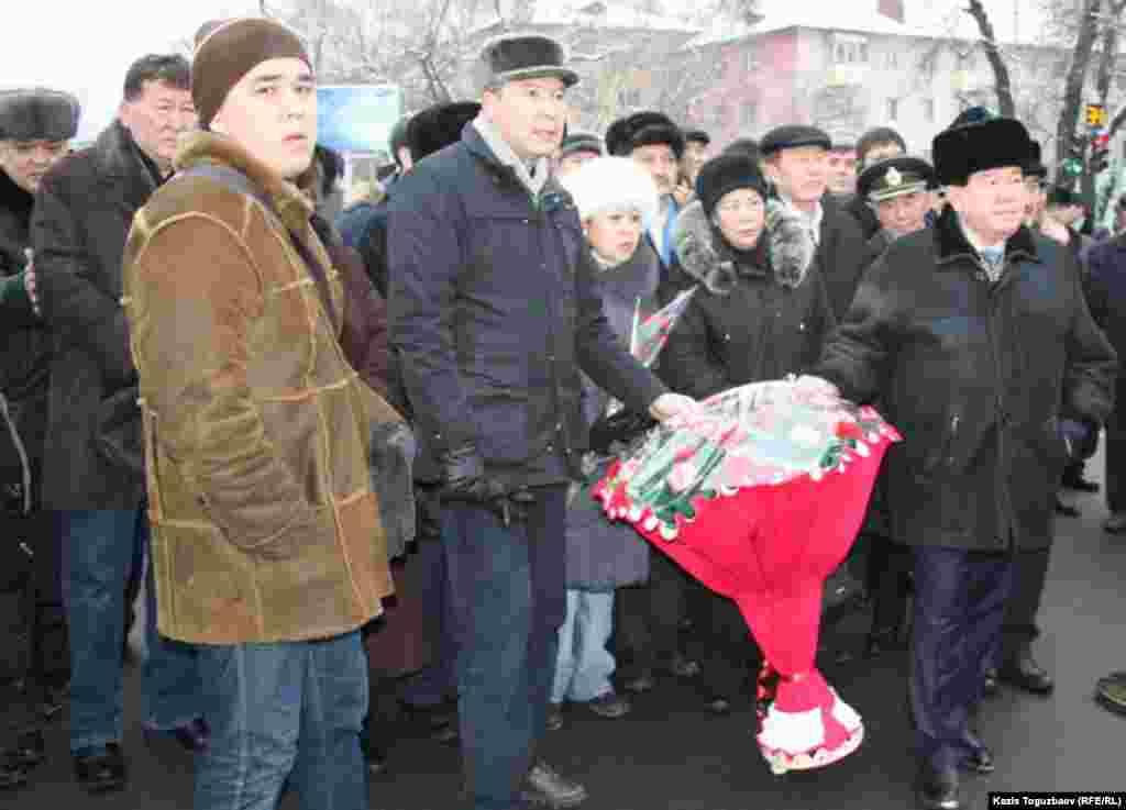 """Лидеры партии """"Руханият"""" Серикжан Мамбеталин (в центре) и Мухтар Шаханов (справа) возлагают цветы к памятнику участникам Декабрьских событий."""