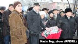 """Бывший лидер партии """"Руханият"""" Серикжан Мамбеталин (в центре) и Мухтар Шаханов (справа) возлагают цветы к памятнику участникам Декабрьских событий. Алматы, 17 декабря 2011 года."""